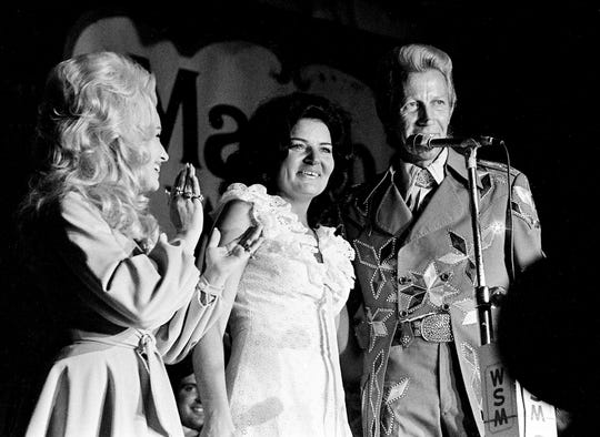 Porter Wagoner, right, and Dolly Parton, left, announce that a surprised Jeanne Pruett, center, is the newest Opry member during the Grand Ole Opry show at the Ryman Auditorium on July 21, 1973.