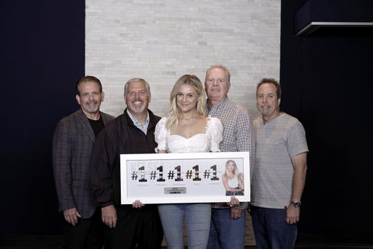 Rick Froio, Gordon Kerr, Kelsea Ballerini, Mike Wilson and Bill Macky pose with Ballerini's plaque celebrating her five No. 1 songs in four years.