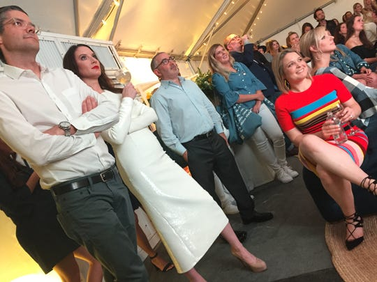 "Clea Shearer (second from left) and Joanna Teplin (seated) watch an episode of their television series ""Master the Mess"" at a premier party at Reese Witherspoon's Nashville store Draper James. Alongside them are Shearer's husband, John, (far left) and Teplin's husband, Jeremy Rubin (center)."