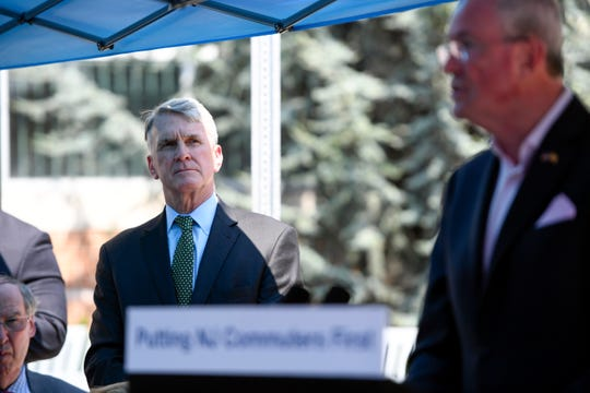 NJ Transit President and CEO Kevin Corbett, left, listens as Governor Phil Murphy, right, holds a press conference before signing an executive order requiring NJ Transit to share certain metrics such as on-time performance and train cancellations at the Bay Street station on Monday, August 19, 2019, in Montclair.