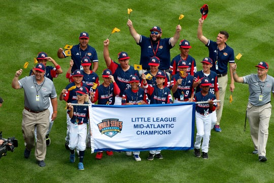 FILE - the Mid-Atlantic Region Champion Little League team from Elizabeth, N.J. participates in the opening ceremony of the 2019 Little League World Series baseball tournament in South Williamsport, Pa. With each game it plays at the Little League World Series, the Elmora Youth League team from Elizabeth, New Jersey, shares the memory of Thomas Hanratty, a state trooper who was killed during a traffic stop in 1992. (AP Photo/Gene J. Puskar, File)