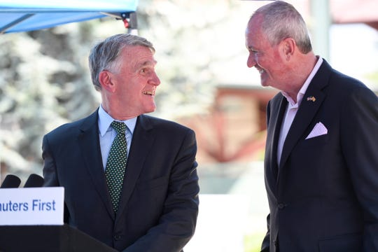 NJ Transit President and CEO Kevin Corbett, left, and Governor Phil Murphy smile at each other during a press conference announcing the signing of an executive order requiring NJ Transit to share certain metrics such as on-time performance and train cancellations at the Bay Street station on Monday, August 19, 2019, in Montclair.