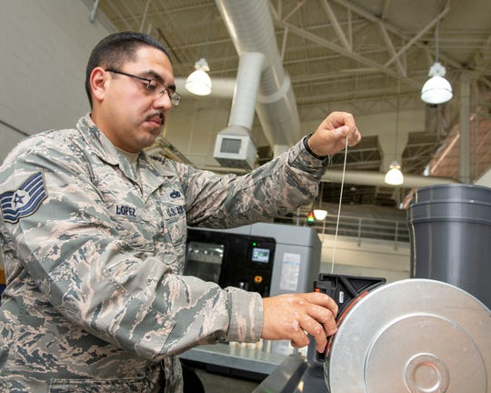 U.S. Air Force Tech. Sgt. Rogelio Lopez, 60th Maintenance Squadron assistant aircraft metals technology section chief, loads Ultem 9085 material into a canister for use in the Stratasys F900 three-dimensional printer Aug. 15, 2019, Travis Air Force Base, California. Travis AFB is the first field-unit location in the Air Force to have the Stratays F900 3-D industrial printer certified by the Federal Aviation Administration and Air Force Advanced Technology and Training Center for use on aircraft replacement parts.