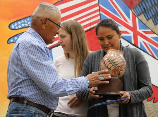 Deidra Benally, right, receives an award from Charley Long Sr., member-at-large for the Navajo Preparatory School Board of Trustees, during a ceremony for International Baccalaureate Diploma Programme graduates on Aug. 19 in Farmington. Benally's daughter, Kelly Charley, was the school's first IB graduate in 2017.