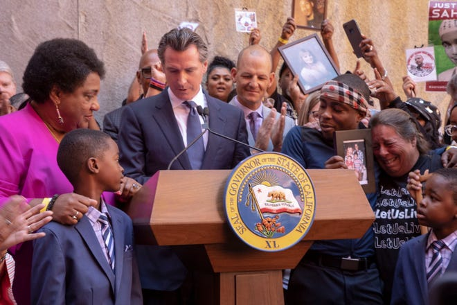 Calif. Gov. Gavin Newsom signs police use-of-force bill AB 392, surrounded by legislators, families and advocates on Monday in Sacramento.
