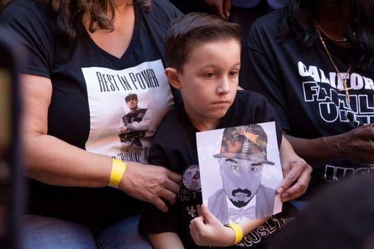 A child in the crowd holds a photo of a lost loved one, as Calif. Governor Gavin Newsom signs AB 392, landmark police-use-of-force legislation