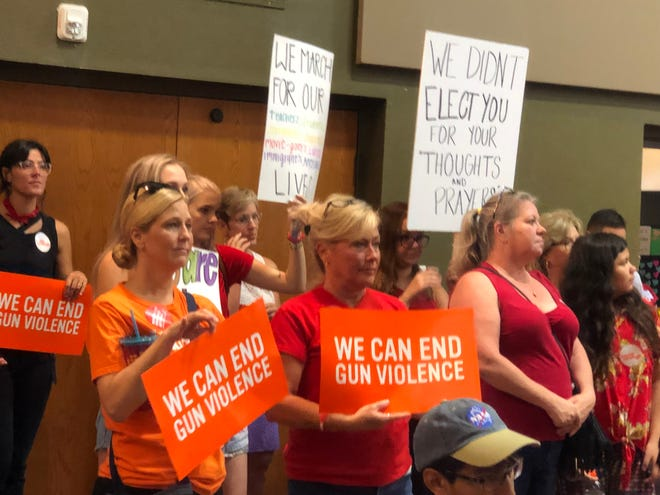 Rally-goers hold up signs at the Moms Demand Action rally on August 18 that advocated for stricter gun laws.