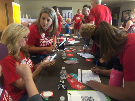 Volunteers help people sign up to be on the mailing list at a front table at the Moms Demand Action rally for common sense gun laws.