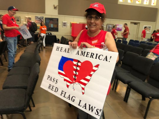 In this August 2019 file photo, Cynthia Engstrom holds her sign with a broken heart over a broken America, advocating for passing red flag laws at a Moms Demand Action Rally in Arizona.
