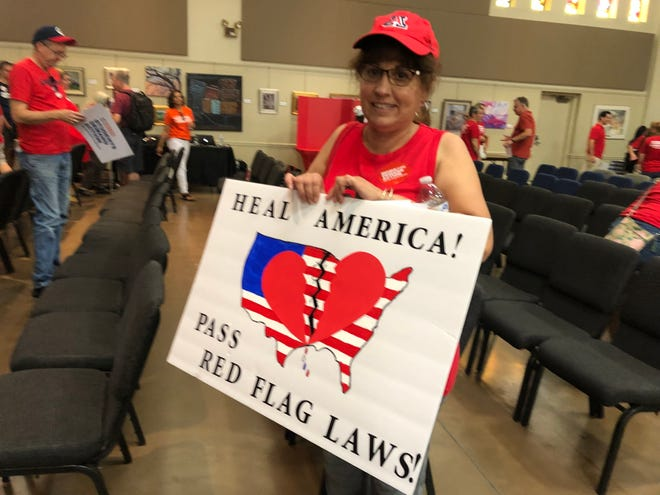 Cynthia Engstrom holds her sign picturing a broken heart over a broken America, advocating for passing red flag laws at the Aug. 18 Moms Demand Action Rally in Glendale, Arizona.