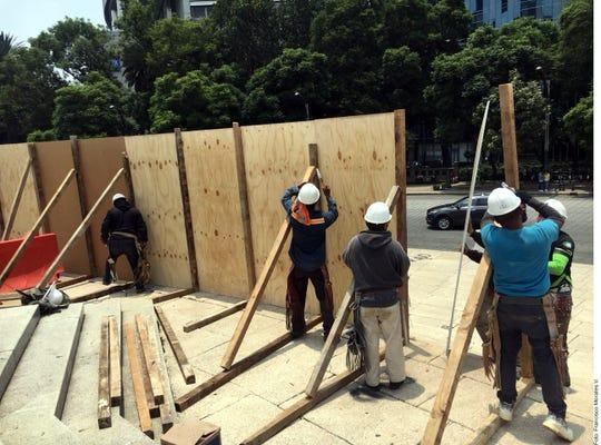 Trabajadores cercan el monumento con madera.
