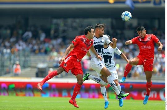 Jugadores de Pumas y Veracruz pelean un balón dividido en el aire.