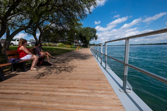 Stephanie Cinner and Diana Beauchamp sit with Zoe, an 8-year-old Golden Doodle, on a bench along the boardwalk in St. Clair Monday, Aug. 19, 2019. A dedication ceremony is being held for the renovated boardwalk in St. Clair's Palmer Park at 3:30 p.m. Sunday.