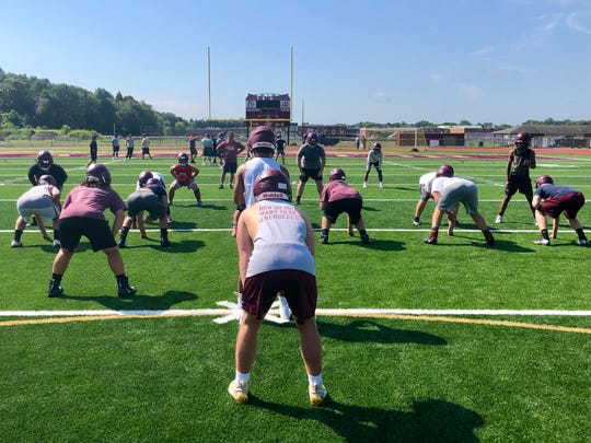 Kwincey Pease readies to take the snap during the Arlington football team's opening practice on Aug. 19.