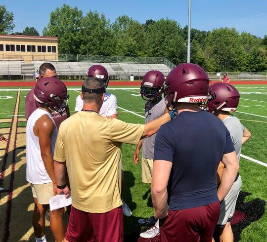 Arlington football coach Mike Morano huddles his offense to call a play during their Aug. 19 practice.