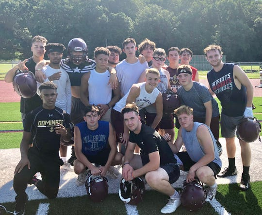 A group of Arlington High School football players pose together during a break at their opening fall practice on Aug. 19.