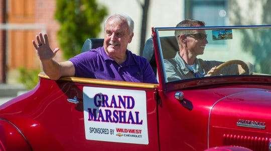 Parade Grand Marshall Jim Sanford waves to the crowd.