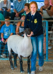 Sarah Thran, from the Smith Valley FFA, walks her sheep during the livestock show.