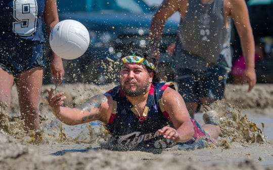 A player dives after the ball during the mud volleyball competition.