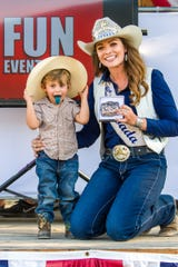 Samuel Watson, 2, sticks out his tongue while receiving a belt buckle for winning his age category in the Littlest Cowboy contest from Jennifer Fisk, Miss Rodeo Nevada.