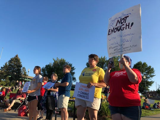 Rally-goers hold signs at a rally for gun reform in central Sioux Falls on Sunday evening. Nearly 100 people attended the rally.