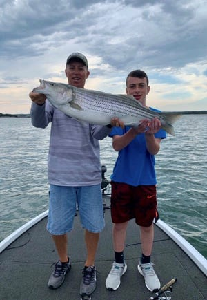Tony Weldele, left, owner of Rainbow Chasers Guide Service, shows off the 25-pound striped bass caught by Table Rock Lake visitor  Zach Baruch, 14, right.