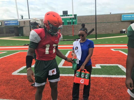 Tia Huie gives water to quarterback Resean McKay to keep him hydrated during practice.