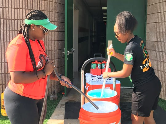 FAMU student athletic trainers Tiki Hemingway and Tia Huie mix Gatorade prior to practice.