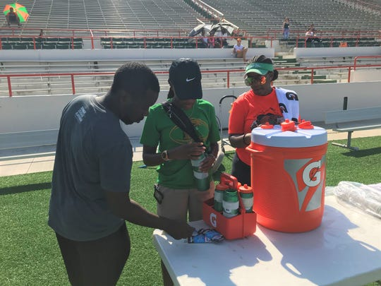 FAMU head athletic trainer Kyle Gaines checks with assistant athletic trainer Kimberly McCartney (center) and Tiki Hemingway filling sports bottles with water and Gatorade during football practice.