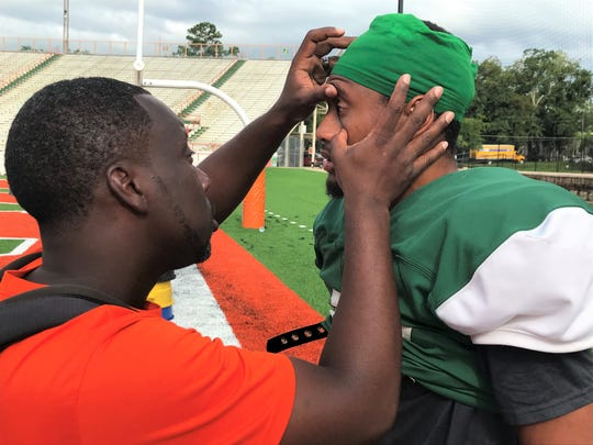 FAMU Athletics head trainer Kyle Gaines checks out the eye of defensive back Kalin Timmons during football practice.