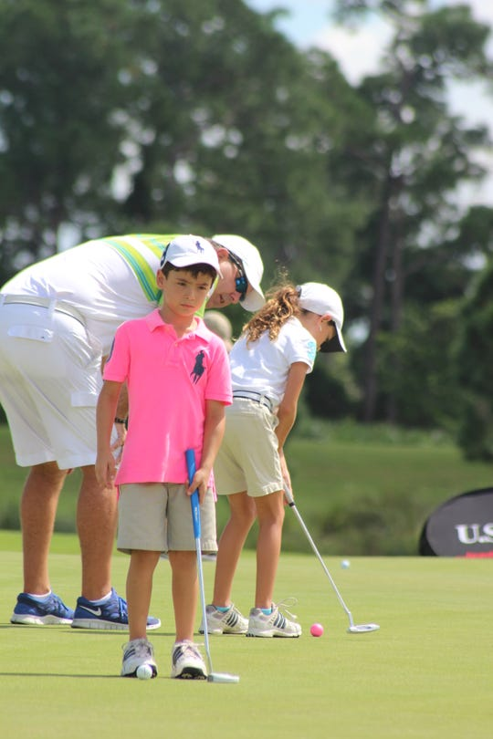 A young Andie Smith (background) practices putting with her dad, Jeff Smith, at a U.S. Kids Golf tournament.