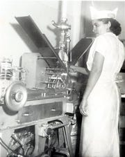 A june 28, 1959, photo caption said that a costly investment in modern machinery enabled the Borden Co. to convert milk into nutritious and low-cost ice cream novelties at its El Paso Plant. The machine shown here automatically assembles and packages ice cream sandwiches under the watchful eye of Mrs. Maria Gomez. The operation was typical of mechanization used throughout the plant.