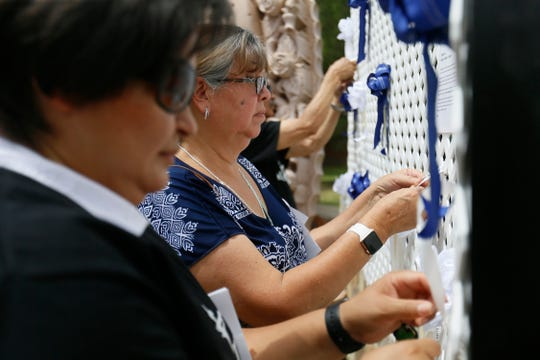 People tie ribbons with prayers written on them on the trellis surrounding the statue of Our Lady of Guadalupe at the Pastoral Center of the Catholic Diocese of El Paso on Monday, Aug. 19, 2019, in memory of the 22 people killed in the Aug. 3, 2019, Walmart mass shooting. Bishop Mark J. Seitz and the staff from the center gathered at the statue to pray for the shooting victims.