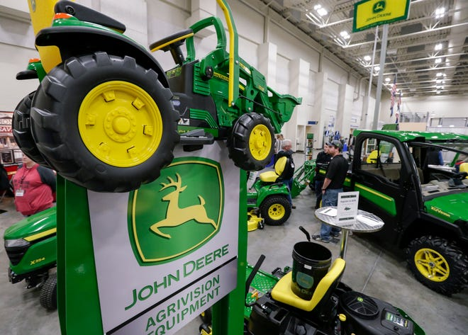 FILE - In this Feb. 23, 2018 file photo, John Deere products, including a toy tractor on the sign, are on display at a home and garden trade show in Council Bluffs, Iowa. John Deere reports financial earnings Friday, Aug. 16, 2019.