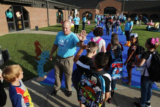 Assistant Principal Chad Kiser gets a high five as students arrive at National Road Elementary School Monday morning. Students were welcomed with a Sailing Through the Year theme.