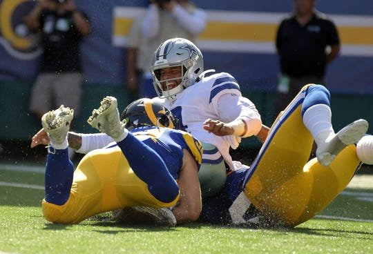 Dallas Cowboys quarterback Dak Prescott (4) is tackled by Los Angeles Rams linebacker Bryce Hager (54) and inside linebacker Natrez Patrick (57) in the first quarter at Aloha Stadium.