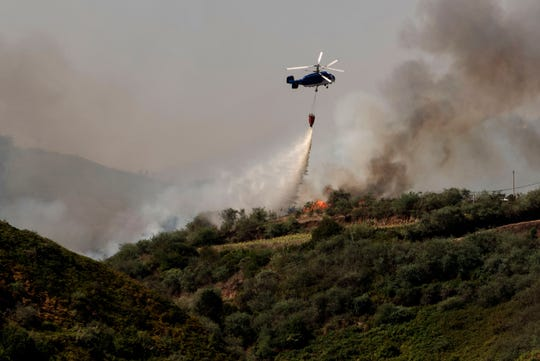 A wildfire in Spain's Canary Islands threw flames 50 meters (160 feet) into the air and has forced emergency services to evacuate more than 8,000 people, authorities said Monday.