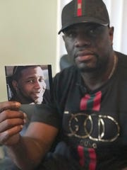 Michael McGlockton holds a photo of his son, Markeis McGlockton, in Clearwater, Fla., on Aug. 7, 2018.