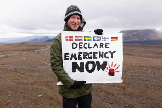 An activist attends the unveiling of a plaque commemorating the loss of Iceland's Okjoekull glacier to climate change during a public ceremony in Borgarfjordur, Iceland, on Aug. 18, 2019.