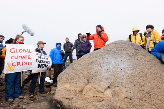 Icelandic author Andri Snaer Magnason, center, holds a speech before the installation of a plaque commemorating the loss of Iceland's Okjoekull glacier to climate change in Borgarfjordur on Aug. 18, 2019.