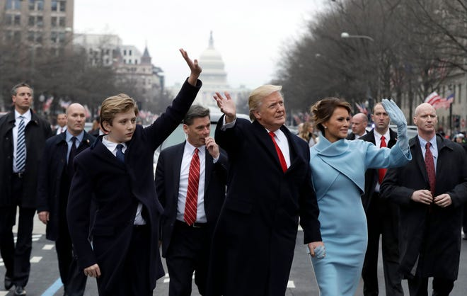 Le président Donald Trump salue ses partisans alors qu'il parcourt le parcours du défilé avec la Première Dame Melania et son fils Barron après avoir prêté serment lors de la 58e inauguration présidentielle le 20 janvier 2017 à Washington, DC