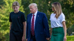 President Donald Trump, flanked by first lady Melania Trump and son Barron, 13, return to the White House following a stay in Bedminster, N.J.