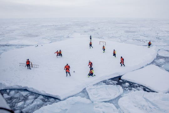 The Crew of patrol vessel KV Svalbard and scientists from the Norwegian Institute of Marine Research play football on ice offshore in the sea around Greenland while two armed guards are looking out for polar bears. Greenland offers tourists arctic-themed activities including glacier hiking and dog sledding.