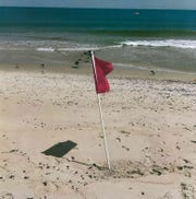 A red flag marks a hazard in the water off of the beach in Manasquan