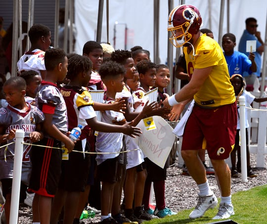 Washington Redskins quarterback Case Keenum slaps hands with young fans on his way out to the practice field Tuesday August 6, 2019. Keenum and Colt McCoy, both from the Big Country, were locked into a head-to-head contest during Redskins training camp in Richmond, Va. over who would eventually be the starting quarterback.