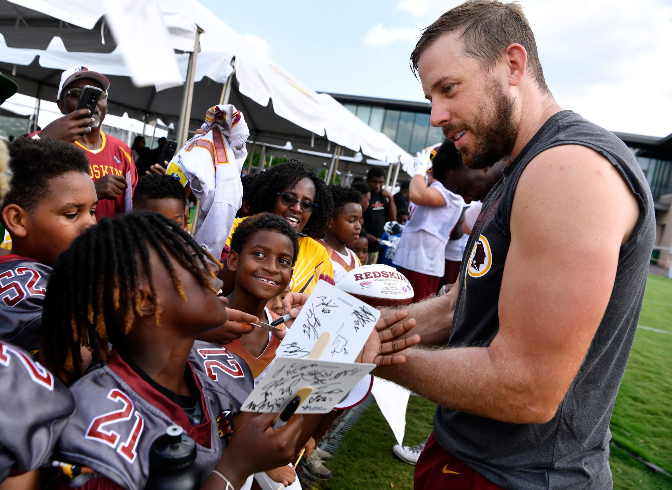 Washington Redskins quarterback Case Keenum signs autographs for children after Tuesday's training camp in Richmond, Va.