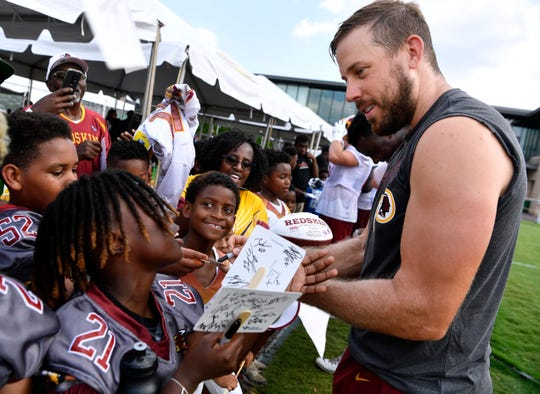 Washington Redskins quarterback Case Keenum signs autographs for children after Tuesday's training camp in Richmond, Va. August 6, 2019.