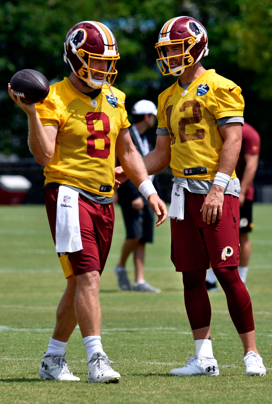 Washington Redskins quarterbacks Case Keenum (left) and Colt McCoy pass each other during training camp in Richmond, Va. Tuesday August 6, 2019.