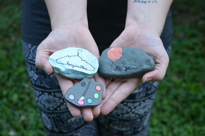 Mia Hoffman holds rocks she painted as part of a community kindness project at her home in Battle Creek on Monday, August 19, 2019.