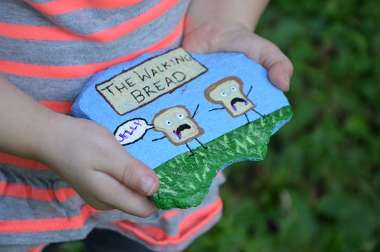 Amelia Hoffman, 3, holds a rock that her mother painted. The rock is going to be placed somewhere in Battle Creek for someone to find, who are then encouraged to post to the Battle Creek Rocks Facebook page before hiding it at a new location.